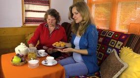 Eftermiddagen med te bakar ihop mormodern och kvinnan tillsammans i rum stock video