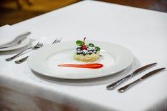 Efterrätt, blåbär och körsbär på en platta Arkivfoto