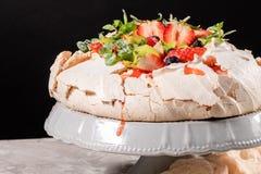Efterrätt för Pavlova marängkaka som göras med jordgubbar, kiwin, blåbär och mintkaramellen royaltyfri fotografi