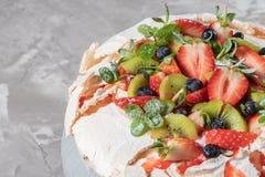 Efterrätt för Pavlova marängkaka som göras med jordgubbar, kiwin, blåbär och mintkaramellen royaltyfria bilder