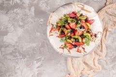 Efterrätt för Pavlova marängkaka som göras med jordgubbar, kiwin, blåbär och mintkaramellen Top beskådar royaltyfri foto