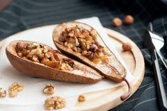 Efterrätt från de bakade päronen med honung och muttrar i en träplatta Royaltyfri Fotografi