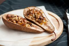 Efterrätt från de bakade päronen med honung och muttrar i en träplatta Royaltyfria Bilder
