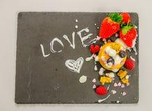 Efterrätt med frukt på en svart stenplatta med en inskriftlo Arkivfoton