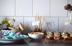 Efterrättbuffé med macarons, morotkakan, kakor och frukt royaltyfri bild