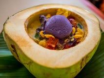 Efterrätten som gjordes med glass, jello, sädesslag och bönor, tjänade som i en kokosnöt Arkivfoton