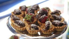 Efterrättstång med blandade chokladsötsaker och bär Jordgubbar i tartlets som täckas med choklad arkivfilmer