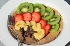 Efterrätt av kiwin, jordgubben, bananen och choklad med gaffeln Fotografering för Bildbyråer