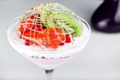 Efterrättglass med en jordgubbe och en kiwi Arkivfoton