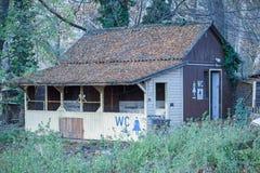 Eftersatt byggnad för offentlig toalett för campingplats trä royaltyfri bild
