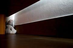 Eftersatt dockanedgång i det mörka hörnet under sängen royaltyfria bilder