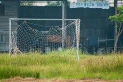 Eftersatt tom fotbollfotboll förtjänar på fältet, oanvänt, förfallet gammalt mål Royaltyfri Bild