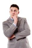Eftertänksam affärsman med handen på hakan Arkivfoto