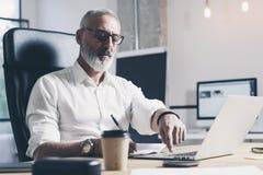 Eftertänksam affärsman som arbetar på det moderna coworking kontoret Säker man som använder den moderna mobila bärbara datorn Arkivfoton