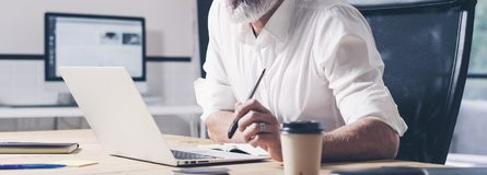 Eftertänksam affärsman som arbetar på det moderna coworking kontoret Säker man som använder den moderna mobila bärbara datorn wid Arkivbilder