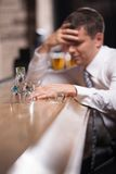 Eftertänksam affärsman som har drinken i flott stång royaltyfri fotografi