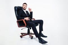 Eftertänksam affärsman som i regeringsställning sitter stol- och innehavmobiltelefonen royaltyfri foto