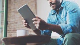Eftertänksam afrikansk man som använder minnestavlan för video konversation, medan koppla av på soffan i modernt kontor Begrepp a royaltyfri foto