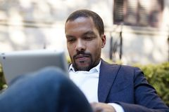 Eftertänksam amerikansk afrikansk affärsman i informell kläder som arbetar på den soliga gatan på det elektroniska handlagblocket Fotografering för Bildbyråer