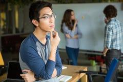 Eftertänksam asiatisk man i exponeringsglas som tänker och arbetar med kollegor Royaltyfria Foton