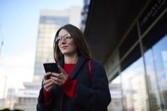 Eftertänksam charmig hipsterflicka i moderiktiga exponeringsglas som pratar med vänner i sociala nätverk Arkivfoton
