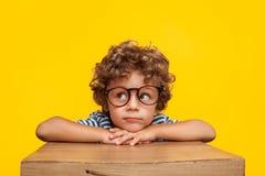 Eftertänksam charmig pojke på studiobakgrund Royaltyfri Bild