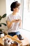Eftertänksam dam i hatt som dricker ny-bryggat kaffe arkivbilder