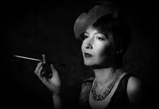 Eftertänksam dam med en cigarett Royaltyfria Bilder