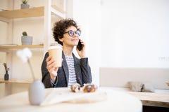 Eftertänksam dam som kallar på telefonen i kafé royaltyfria bilder