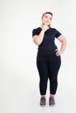 Eftertänksam fet kvinna i sportswearen som ser upp royaltyfri fotografi