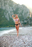 Eftertänksam flicka som går på sommarhavsstranden i bikini royaltyfria bilder