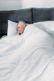 Eftertänksam hög man som hemma ligger i säng Royaltyfri Foto