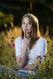 Eftertänksam kvinna i blommande äng Royaltyfri Foto