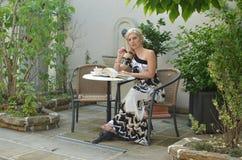 Eftertänksam kvinna i en trädgård Royaltyfri Bild