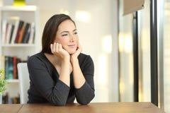 Eftertänksam kvinna som hemma kopplar av Royaltyfri Fotografi