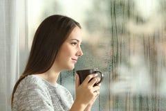 Eftertänksam kvinna som ser till och med ett fönster royaltyfri foto