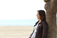 Eftertänksam kvinna som tänker på stranden i vinter Arkivbilder