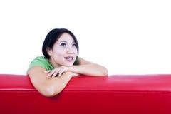 Eftertänksam kvinnlig för närbild på den isolerade röda soffan - Royaltyfri Bild