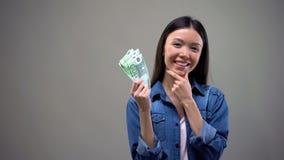 Eftert?nksam le kvinna som rymmer euro som isoleras p? gr? bakgrund, cashback arkivbilder