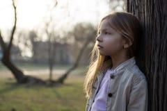 Eftertänksam liten flicka bredvid ett träd arkivfoto