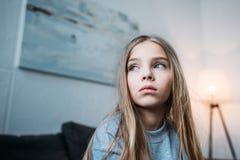 Eftertänksam liten flicka i pyjamas som bort hemma ser arkivbild