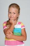 Eftertänksam liten flicka på den gråa bakgrunden Royaltyfri Bild