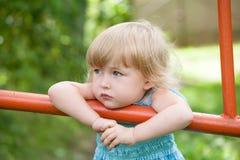 Eftertänksam liten flicka på utomhus- bakgrund för sommar royaltyfri bild