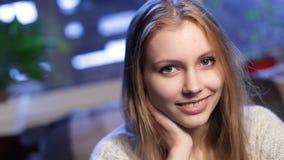 Eftertänksam lycklig ung kvinna som minns och ler lager videofilmer