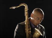 Eftertänksam man med saxofonen som ner ser Arkivfoton