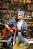Eftertänksam manlig gitarrist som framkallar hans musikexpertis arkivfoto