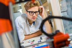 Eftertänksam manlig tekniker som studerar den tredimensionella skrivaren Royaltyfria Foton