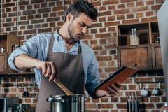eftertänksam matlagning för ung man royaltyfri bild