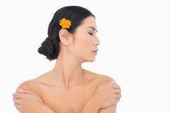 Eftertänksam modell med den orange blomman i hår som trycker på hennes skuldror Royaltyfria Bilder
