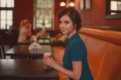Eftertänksam nätt flicka i klassiskt sammanträde för elegant klänning på kafét som går att dricka kaffe royaltyfri fotografi